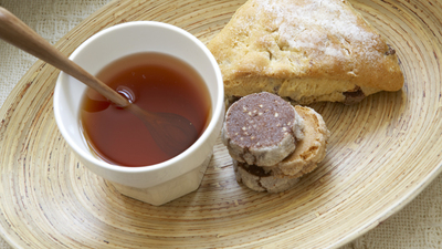 Pastries and cup of tea on wooden plate, close-up