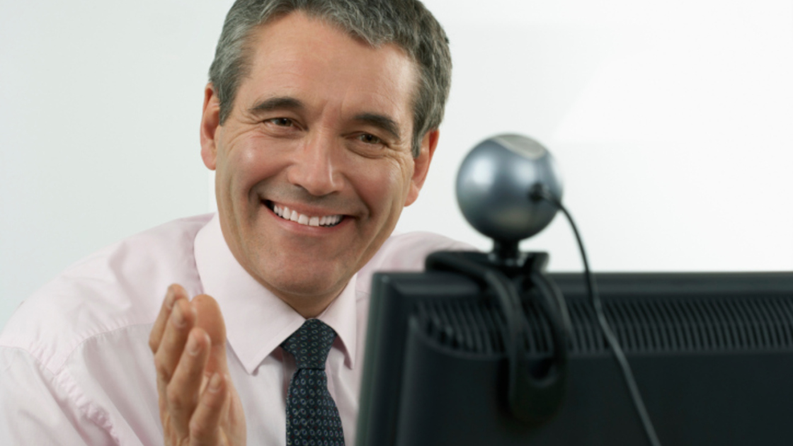 Businessman Smiling at Webcam
