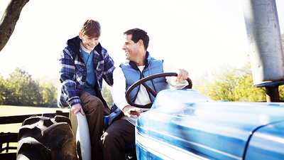 Father and son driving tractor