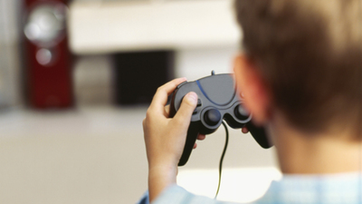 rear view of a boy playing a video game