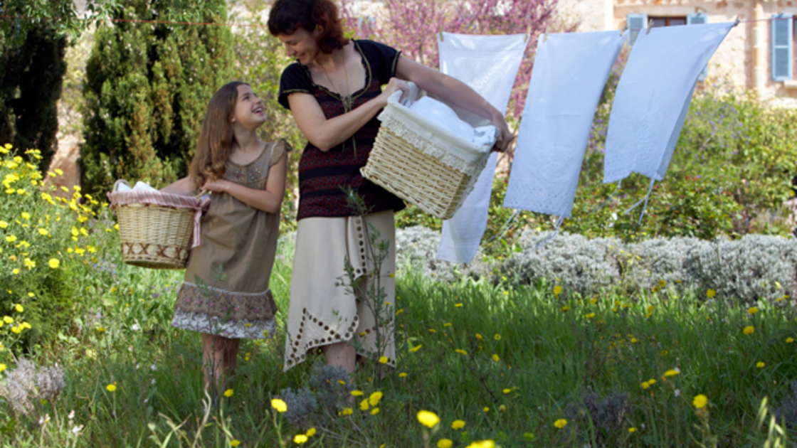 Mother and daughter (8-9) with baskets in domestic garden.