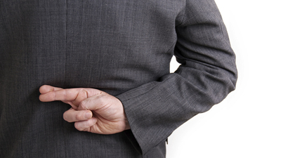 A conceptual image of a business man with his fingers crossed behind his back.