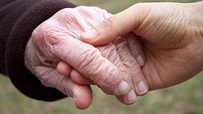 Young woman's hand holding old woman's hand.