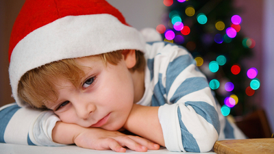 Little boy in santa hat with christmas tree and lights on background, dreaming