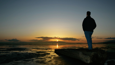 lonely man on beach in silhouette at sunset (XL)