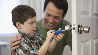 Father and son fixing doorknob