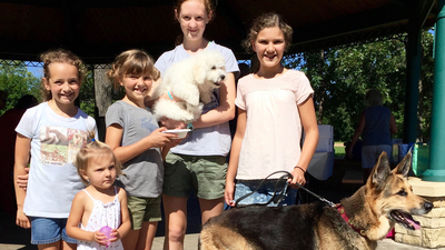 Pictured (L to R): Katelyn Aldrich, Violet Kaleho, Chloe Kaleho, Erica Anderson (holding Ozzie the Dog in her arms), Sofia Kaleho (holding Kaia the dog on a leash).