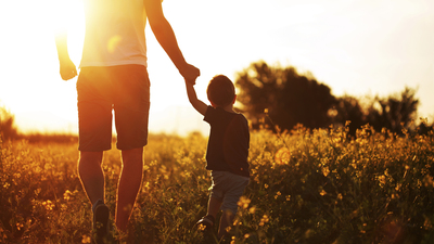 Photo of little boy holding his father hand and walking at the field in the sunset