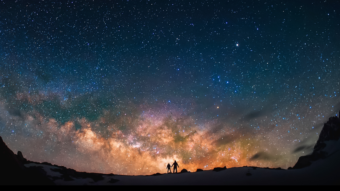 Silhouttes of the people standing together holding hands against the Milky Way in the mountains.