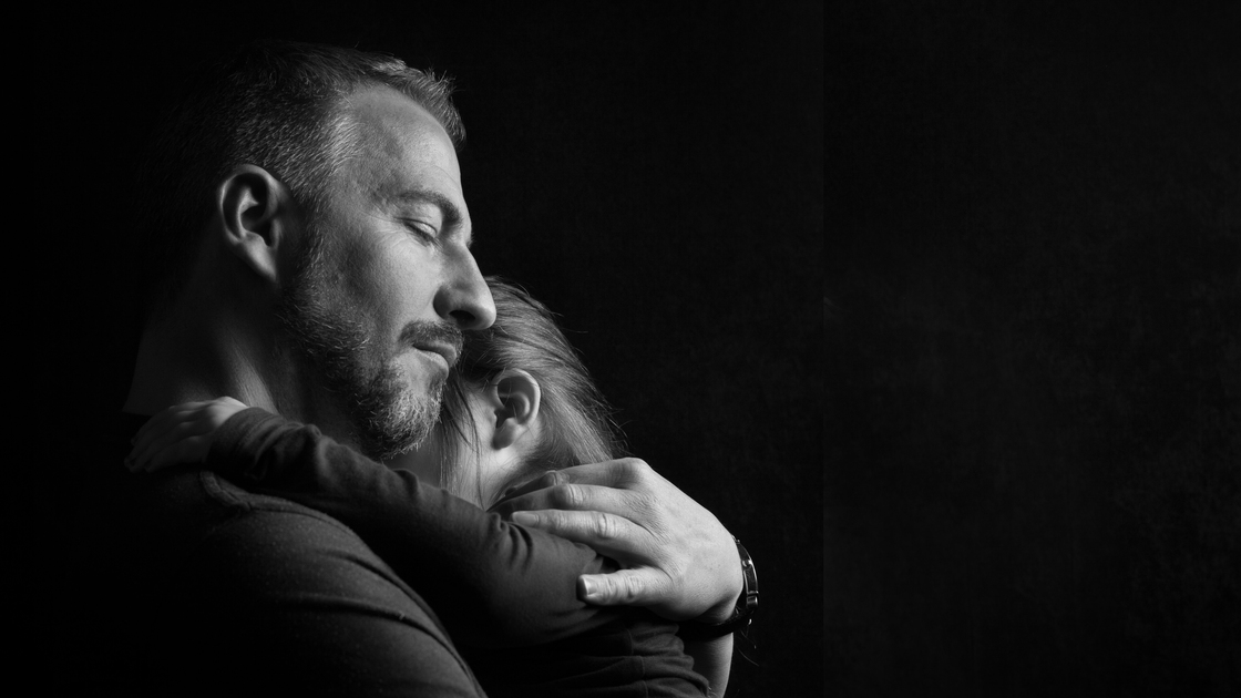 Touching Heart Felt Black and White Image of Father with Eyes Closed Hugging Young Daughter Tenderly with Dark Background with Copy Space