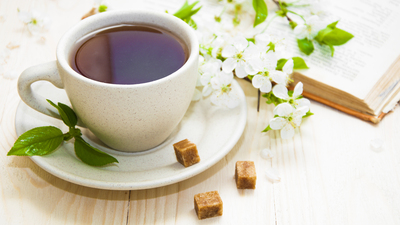 A cup of tea with spring flower cherry blossom and old book on a wooden background