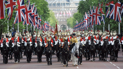 London, United Kingdom - June, 13th 2006:Mounted Horse guards parade through London beneath British flags in a ceremonial parade