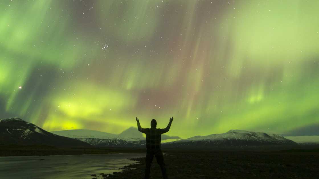 aurora borealis on iceland, human silhouette in foreground, some ISO-noise