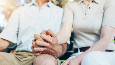 Cropped shot of mature couple holding hands while sitting together on a park bench. Focus on hands.