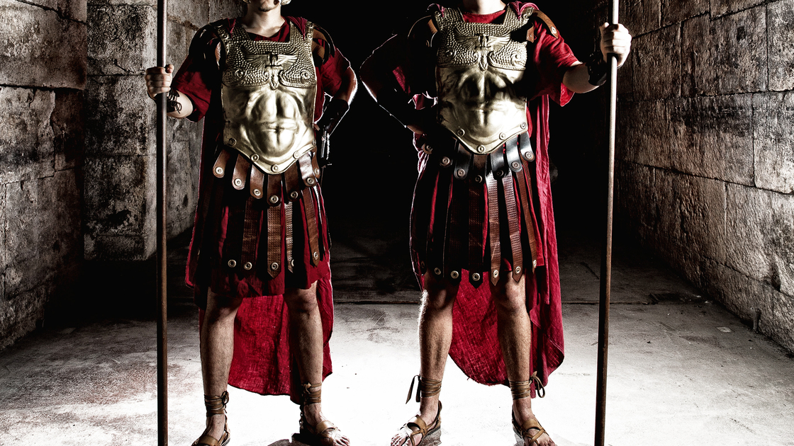 Two Roman soldiers holding spears in vestibule.