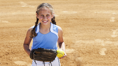 Girl (9 years) playing softball, standing on pitcher's mound.