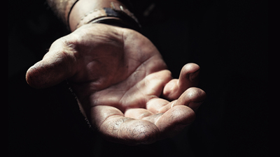 Hand emerging from the dark. Wrist and the gentle open hand of a hardworking man extend from the darkness. The hand is faintly cupped and the fingers are pressed together. Background in soft focus.