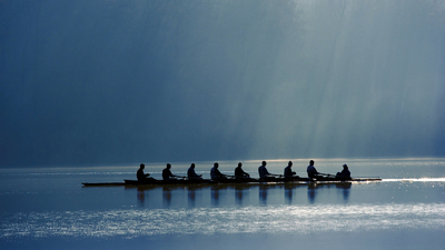 A canoe team rowing with power in order to win the competition. On background morning light through the forest.