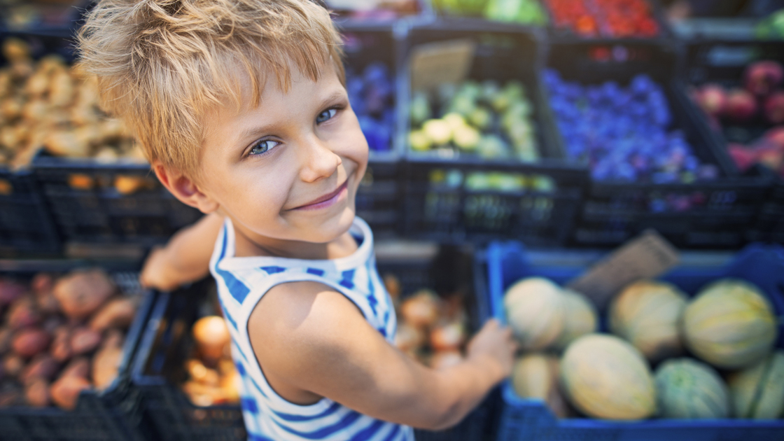 Happy little boy buying local groceries food at the tuscanian farmer's market at Cecina. Italy, Tuscany.