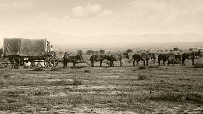 Vintage photograph of an old fashioned covered wagon pulled by a team of horses.