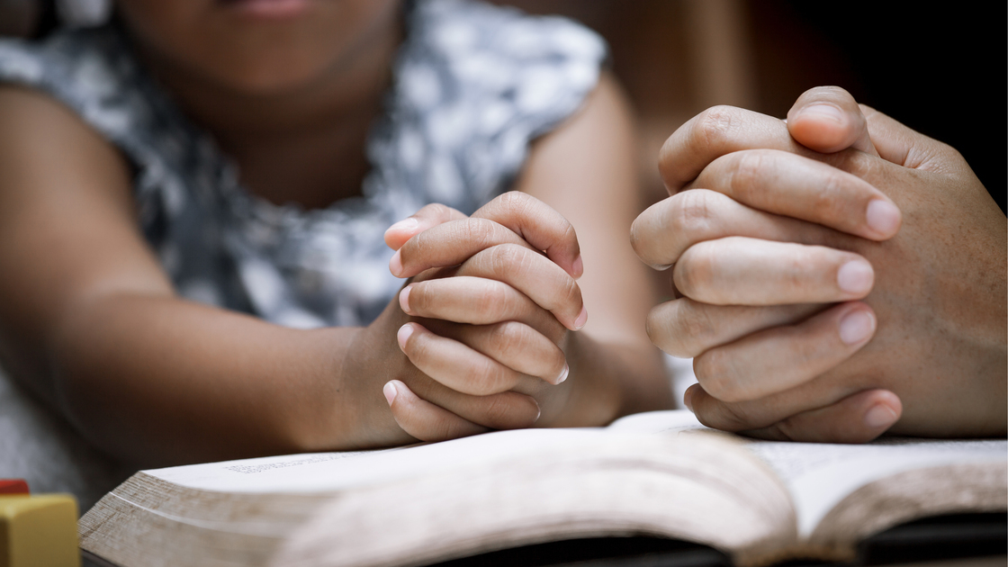 Mother and little girl hands folded in prayer on a Holy Bible together  for faith concept in vintage color tone