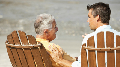 Rear view of senior man (60s) talking with adult son (40s), sitting on adirondack chairs on the beach.