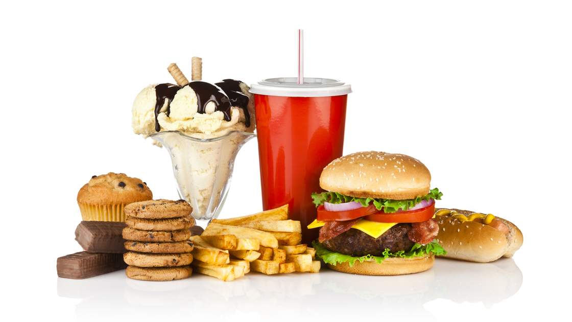 Group of unhealthy food isolated on white background. The composition includes, candy bar, muffin, cookies, ice cream, french fries, a glass of soda, hamburger and a hot dog. This is an unhealthy food rich in carbohydrates, sugar and calories.  DSRL studio photo taken with Canon EOS 5D Mk II and Canon EF 70-200mm f/2.8L IS II USM Telephoto Zoom Lens