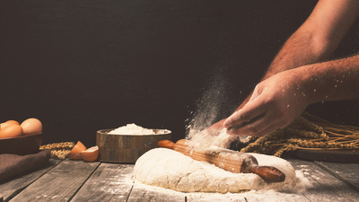 Men hands sprinkle a dough with flour close up. Man preparing bread dough