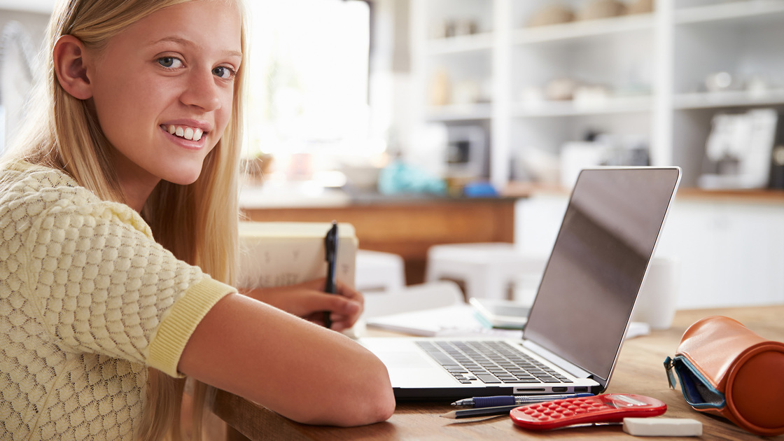 Girl using laptop computer at home, smiling to camera