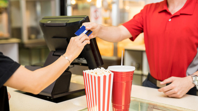 Closeup of a young woman handing over her credit card to pay for some snacks at the concession stand in a movie theater, fundraiser, 16x9