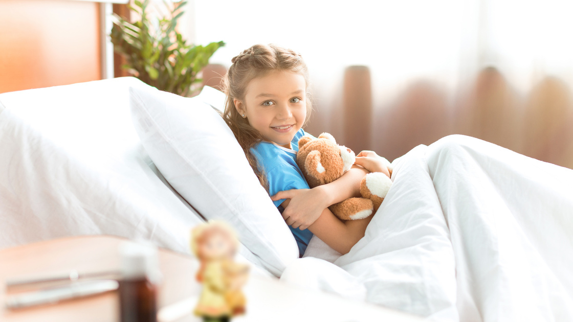 Cute little girl lying in hospital bed with teddy bear and smiling at camera