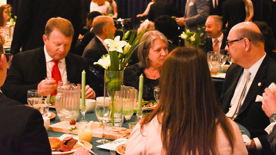 ACT Speech Banquet 2019, students and faculty conversing at table, 16x9