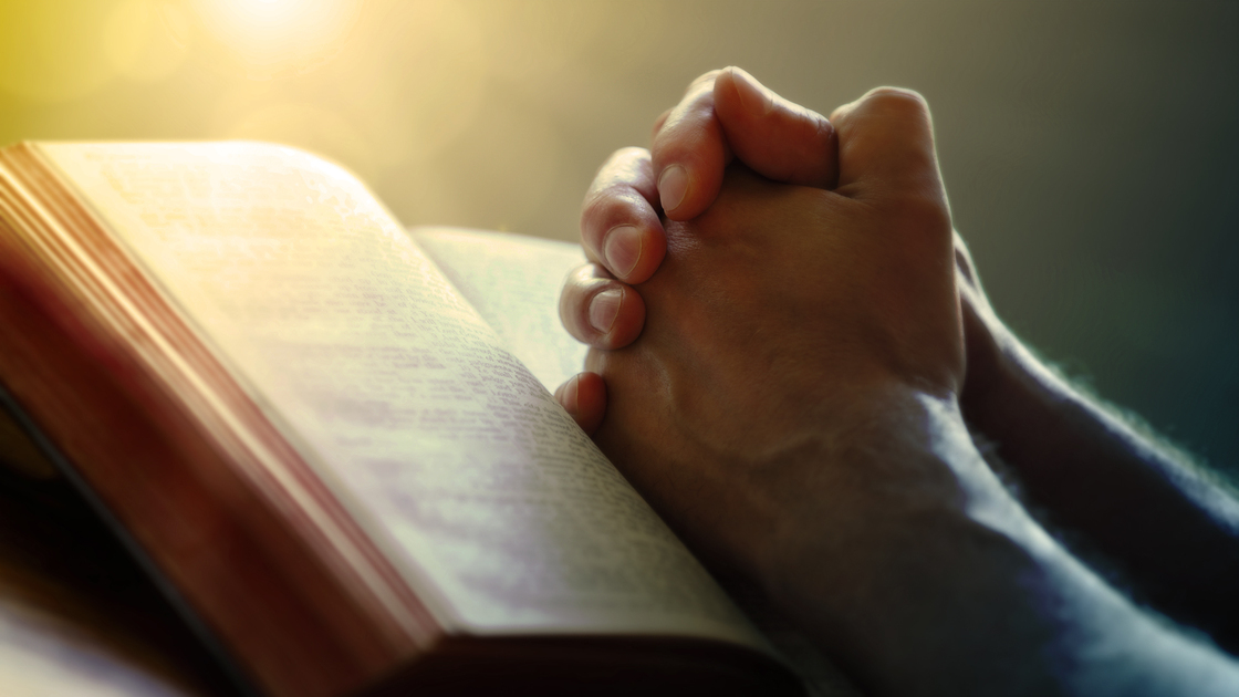 Hands folded in prayer on a Holy Bible in church concept for faith, spirtuality and religion