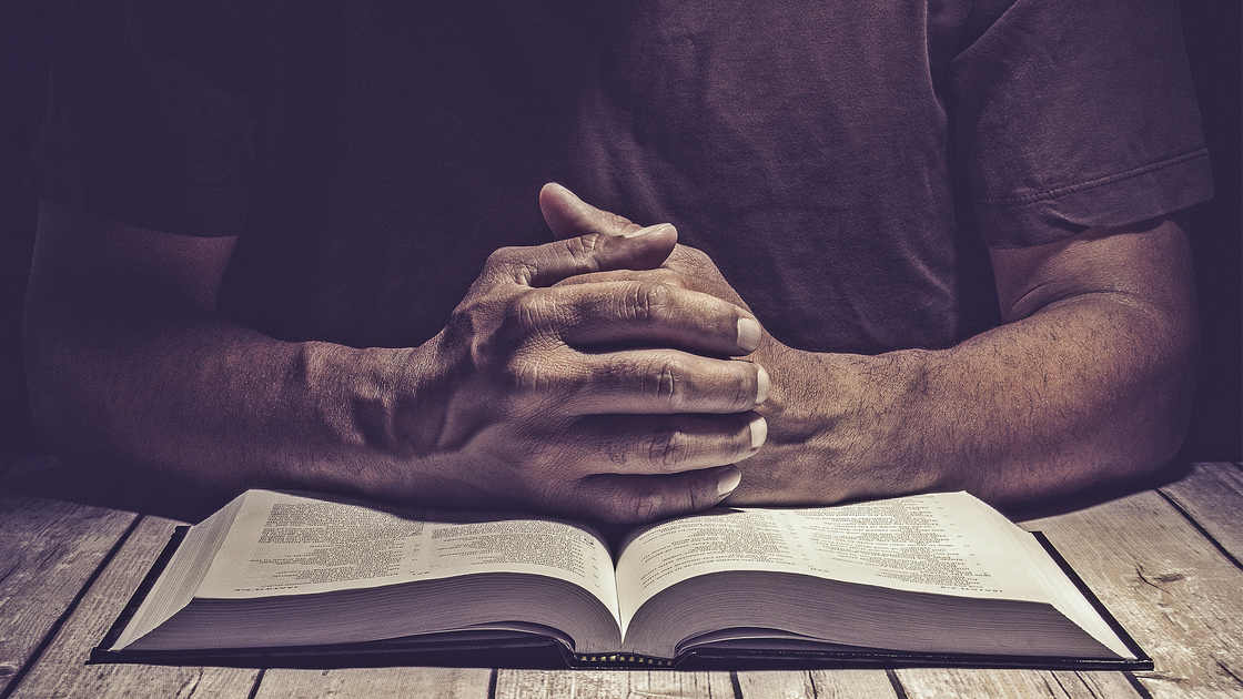 Man praying on a wooden table with an open Bible.