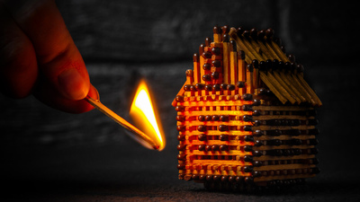 hand with a burning match sets fire to the house model of matches, risk, property Insurance protection or ignition of combustible materials concept.