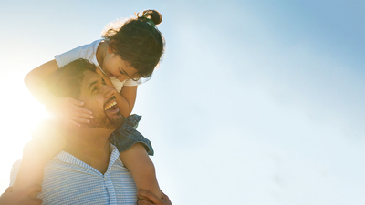 A young girl sits on her dad's shoulders, looking at each other, both smiling outdoors in the sun