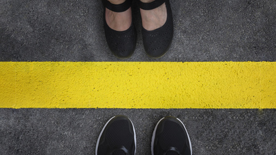 Legs of a couple standing opposite each other divided by the yellow asphalt line top view