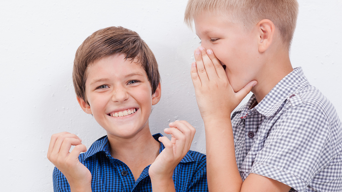 Teenage boy whispering  a secret in the ear of surprised  friend on white  background