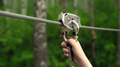 Zip line activity. Hands holding carabiner on zip line in forest.