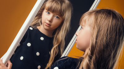 child in the Studio posing in fashionable clothes to looks in a mirror
