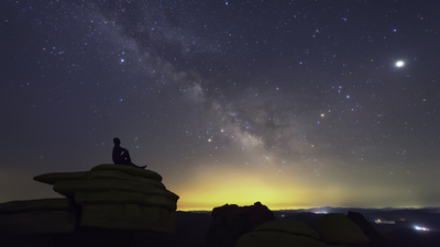 Man sitting on the rocks in solitude under the cover of dark, clear sky and looking at Milky Way galaxy while thinking about his existence.