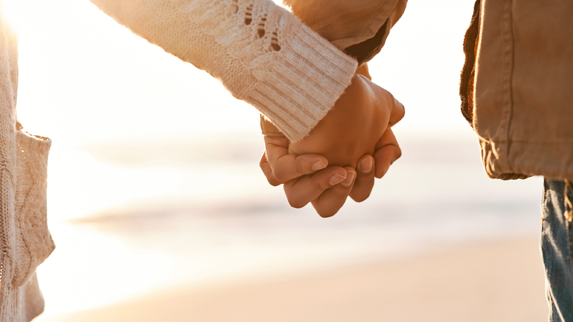 Cropped shot of an unrecognizable couple holding hands on the beach