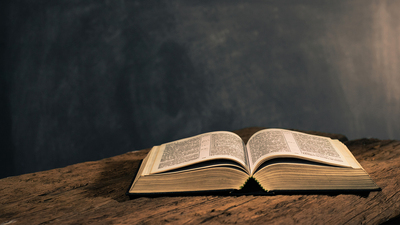 Bible on a old oak wooden table. Beautiful dark background. Religion concept