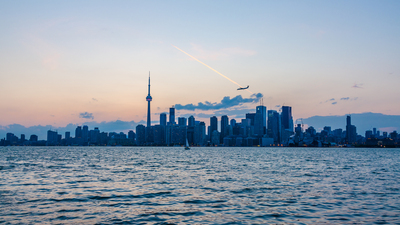 Skyline of Toronto over Ontario Lake at sunset with sail boat
