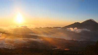 Image of Mount Agung volcano in Bali, photographed in the sunrise from the top of another volcano - Mount Batur. Beautiful sunrise above the clouds in the dawn.