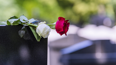 Close View of Headstone In Cemetery With Red Rose Flower. Concept Of Funeral, Death And Loss.