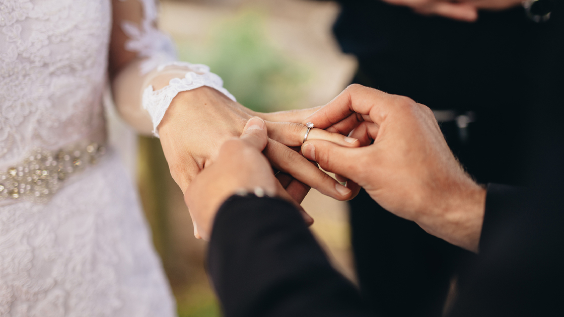 Closeup of groom placing a wedding ring on the brides hand.  Couple exchanging wedding rings during a wedding ceremony outdoors.