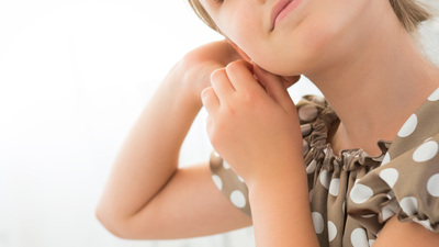 7 or 8 years old little girl with blond hair posing pointing with earrings
