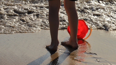 A child children's feet on the beach plays with water with a toy bucket