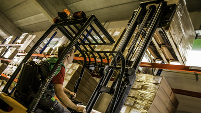 Wide shot of warehouse worker lifting a pallet of goods with a forklift in a colorful warehouse setting. Low angle view.